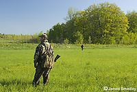 Hunters in camouflage scouting field for wild turkeys