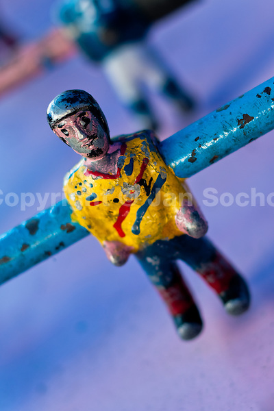 A table football player figure, with a painted blue shirt and peeled surface, is seen inside the table football box on the street of Otavalo, Ecuador, 28 June 2010. Table football, also known as futbolin in Latin America, is a widely popular table-top game in Ecuador. During the annual fairs, the rusty old outdoor-designed tables, fully ocuppied by excited children, may be found on all public places, particularly on the squares and in the parks. Human players use figures mounted on rotating bars to kick the small plastic ball into the opposing goal. Each team of 1 or 2 human players controls 4 rows on its side of the table. The game ends when one team scores a predetermined number of goals. In 2002, the International Table Soccer Federation (ITSF) was established to promote the sport of table football.