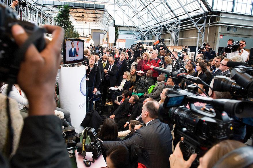 Denemarken, Kopenhagen, 18 dec 2009.COP15, Copenhagen.Sfeerbeeld van laatste dag van de klimaatconferentie..Barack Obama spreekt tot de UN. Iedereen wil dat horen en zit voor tv-schermen. TVploegen filmen tv schermen, want in de zaal mag niemand komen.Foto Michiel Wijnbergh