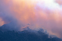870000350 a los angeles county fire fighting helicopter flying through thick smoke performs aerial retardant drop on homes directly in the burn path of the topanga fire in the hills above the san fernando valley in southern california