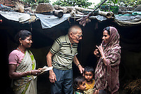Father Laborde speaks with a young mother during his visit to a slum at the Shalimar coal depot in Howrah. West Bengal, India, Arindam Mukherjee/Agency Genesis