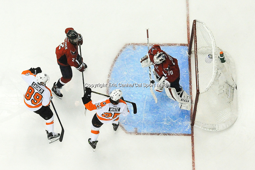 Thursday, April 14, 2016: Washington Capitals goalie Braden Holtby (70) stops a shot as Philadelphia Flyers center Sam Gagner (89) and center Ryan White (25) watch for the reound during game 1 of the first round of the National Hockey League Eastern Conference playoffs  between the Philadelphia Flyers and the Washington Capitals held at the Verizon Center in Washington, DC. Washington defeats Philadelphia 2-0. Eric Canha/CSM