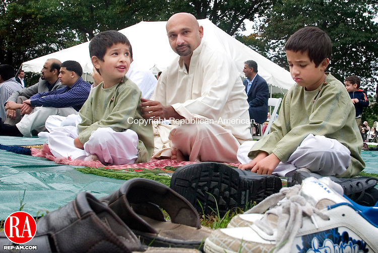 WATERBURY, CT 30 September 2008-093008SV01--Muhammad Masoob of Waterbury and his two sons Joey, 5, and Musa, 7 participates in a ceremony celebrating Eid ul-Fitr at Library Park in Waterbury Tuesday. Muslims around the world celebrate Eid ul-Fitr (eed al-fitter), the three-day festival commonly known as &quot;Eid.&quot; &quot;Eid ul-Fitr&quot; literally means &quot;the feast of the breaking/to break the fast.&quot; The holiday marks the end of Ramadan, the holy month of fasting and is a culmination of the month-long struggle towards a higher spiritual state.<br /> Steven Valenti Republican-American