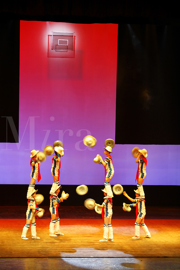 Boys juggling hats at Chinese acrobatic show, Beijing, China, Asia