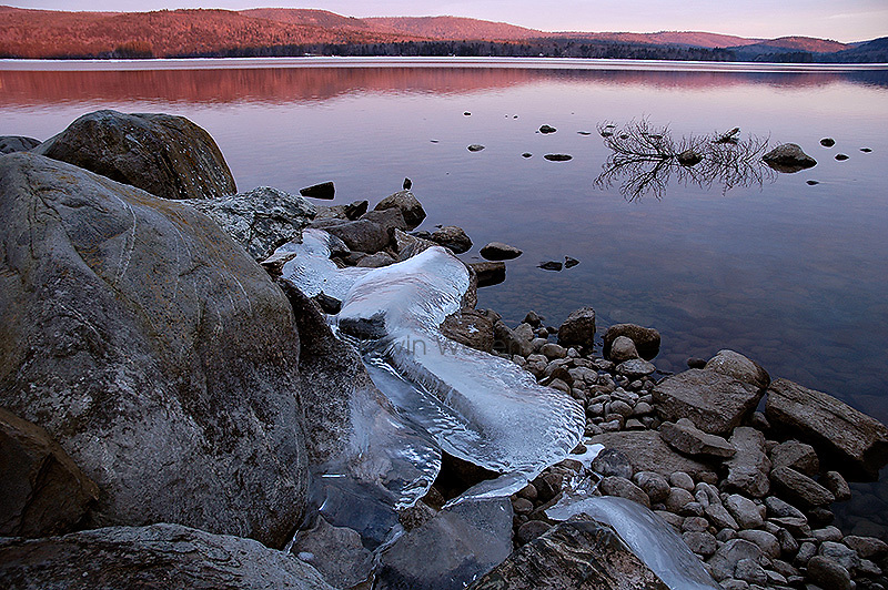 Ice clings to the rocky shore of Long Pond in Belgrade Lakes, Maine. Water flowing through the nearby dam, coupled with mild winter temperatures, have prevented this part of the pond from freezing.