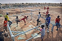 Children play at kickboxing in a 'boxing ring' left behind at an abandoned oil well and pumping station.