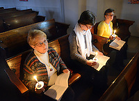 From left, Bonnie Lesh of Hilton, Pennsylvania, Wendy Gogol of Chalfont, Pennsylvania and Fay Wozniak of Chalfont, Pennsylvania hold candles as they participate in the Holy Saturday Easter Vigil and Holy Eucharist services at Good Shepherd Episcopal Church Saturday March 26, 2016 in Hilltown, Pennsylvania.  (Photo by William Thomas Cain)