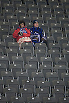 Two home fans attempt to keep warm inside the stadium before Hertha Berlin's match against  Sporting Lisbon at the Olympic Stadium in Berlin in the group stages of the UEFA Europa League. Hertha won the match by 1 goal to nil to press to the knock-out round of the cup. 2009/10 was the the first year in which the Europa League replaced the UEFA Cup in European football competition.