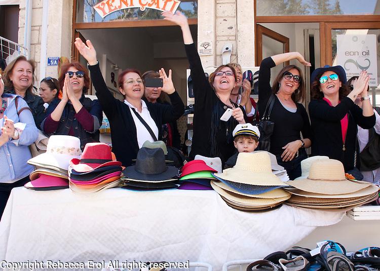Turkish women waving to a procession in Alacati, Turkey