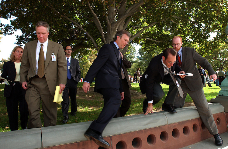 "1terrorist101101 -- Senate Majority Leader Tom Daschle, D-S.D., along with reporters and a security detail hop over wall on the way back to the Capitol after the ""Day of Remembrance"" ceremony."