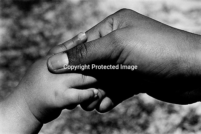 Patricia Lincoln, age 16, holds the tiny hand of her one-year-old daughter Baby Thsepang as she is recovering on February 11, 2002 at the Red Cross Children's Hospital in Cape Town, South Africa. The baby was brutally raped by her father in October 2001 in Loisevale, a poor colored area outside Upington, about 900 kilometers Northwest of Cape Town, South Africa. The country is struggling with a growing problem with abuse of children and babies. (Photo by: Per-Anders Pettersson)