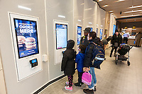 A concierge assists diners at a digital ordering kiosks in a prototype McDonald's in New York, upscaling with minimalist decor and a McCafe, on Wednesday, February 1, 2017.  (© Richard B. Levine)