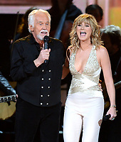 """20 March 2020 - Kenny Rogers, whose legendary music career spanned nearly six decades, has died at the age of 81. Rogers was inducted to the Country Music Hall of Fame in 2013."""" He had 24 No. 1 hits and through his career more than 50 million albums sold in the US alone. He was a six-time Country Music Awards winner and three-time Grammy Award winner. Some of his hits included """"Lady,"""" """"Lucille,"""" """"We've Got Tonight,"""" """"Islands In The Stream,"""" and """"Through the Years."""" His 1978 song """"The Gambler"""" inspired multiple TV movies, with Rogers as the main character. File Photo: 06 November 2013 - Nashville, Tennessee - Kenny Rogers, Jennifer Nettles, Sugarland. 47th CMA Awards, Country Music's Biggest Night, held at Bridgestone Arena. Photo Credit: Laura Farr/AdMedia"""