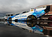 Feb 22, 2019; Chandler, AZ, USA; The car of NHRA funny car driver Tommy Johnson Jr reflects in a rain puddle as the car is towed to the staging lanes during qualifying for the Arizona Nationals at Wild Horse Pass Motorsports Park. Mandatory Credit: Mark J. Rebilas-USA TODAY Sports