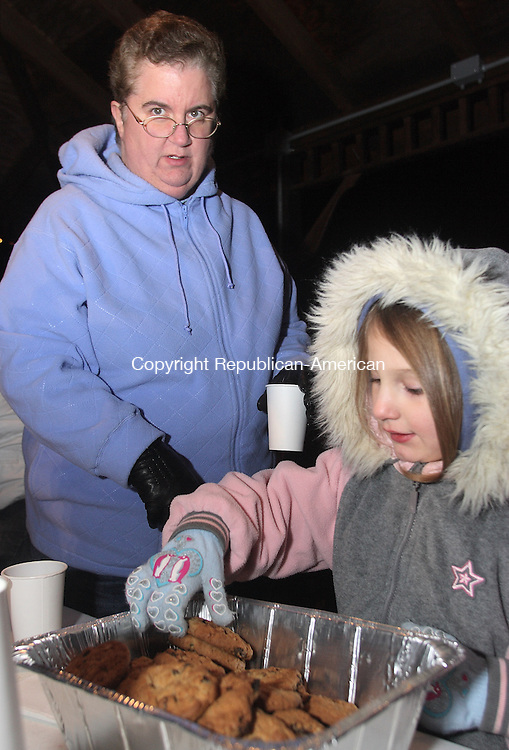 Alexa McDougall selectsa cookie as her grandmother Barbara McDougall looks over while  a hundred children and their parents gathered at the Legion Pool in Seymour Saturday night to enjoy the hot chocolate and cookies and fireworks which signaled the arrival of Santa Claus at the Seymour Land Trust's 12th Annual Christmas Visit of Santa Claus.  Michael Kabelka / Republican-American