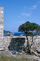 A pair of deck chairs have been placed on the stone terrace overlooking the Pelion peninsula and the Aegean sea