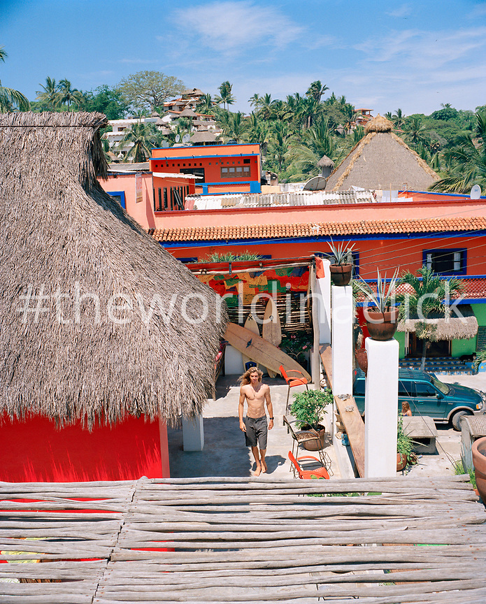 MEXICO, Sayulita, young man walking on the rooftop terrace of his house.