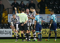 Michael O'Connor (left) of Notts Co tries to show the referee his injury after being handed a red card and sent off during the Sky Bet League 2 match between Notts County and Wycombe Wanderers at Meadow Lane, Nottingham, England on 10 December 2016. Photo by Andy Rowland.