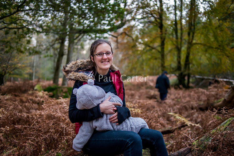 A young woman breastfeeds her baby girl, who is dressed in a winter fleece jumpsuit, during an autumn walk in the woods at dusk.<br /> <br /> The New Forest, Hampshire, England. UK<br /> 03/11/2012