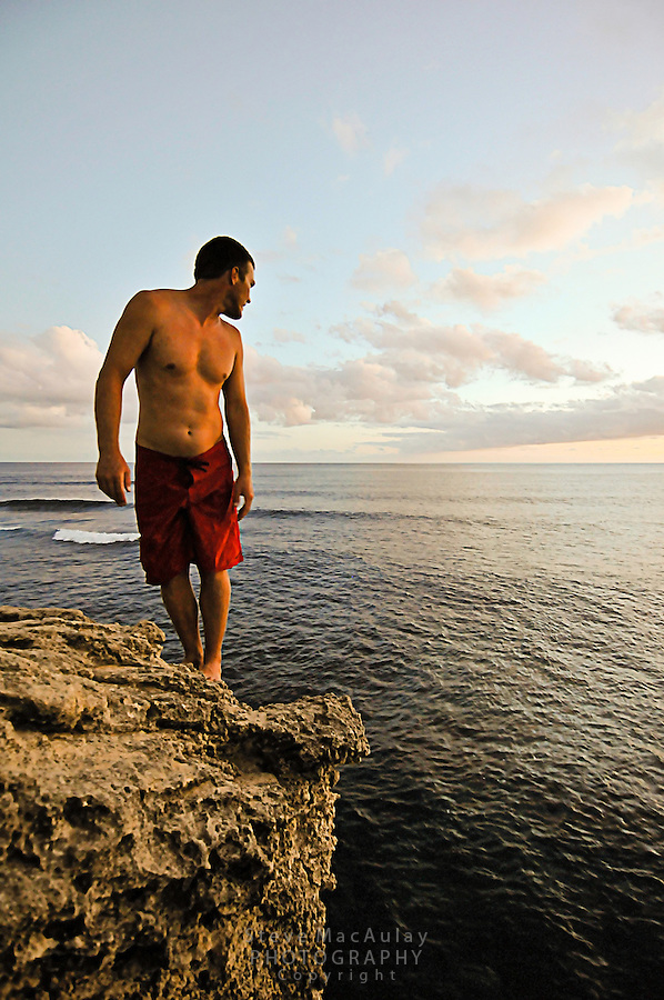 Young man cliff jumping off the bluff at Shipwreck Beach, Poipu, Kauai, Hawaii