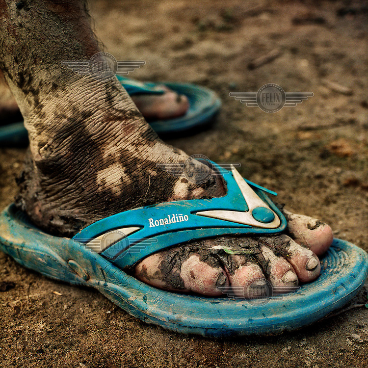 The feet and sandles of a man in a village on the banks of the Urubamba River.