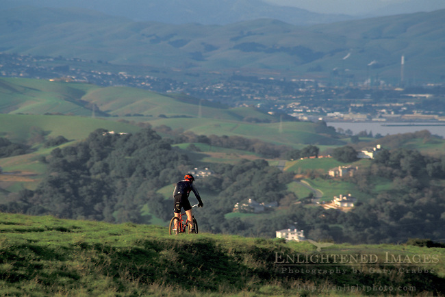 Mountain biker biking in rural green hills in spring, Briones Regional Park, Conta Costa County, California