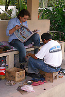 Young man reading a newspaper while getting a shoe shine in Santa Rosa de Copan, Honduras.