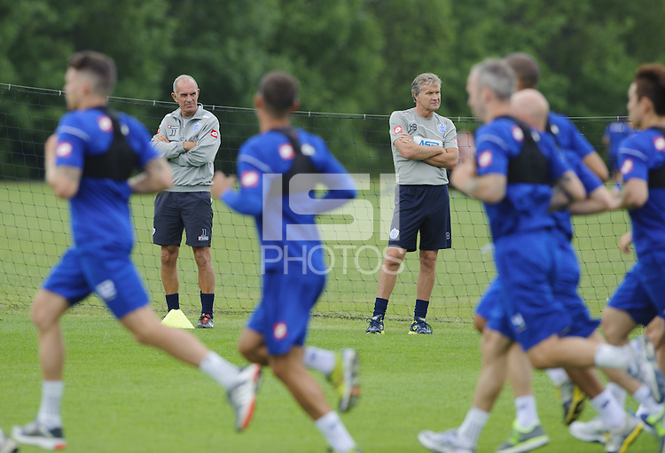 QPR assistants Kevin Bond and Joe Jordan watch the first team train