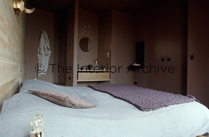 The built-in cupboards, wood-lined walls and niche with washbasin allow this bedroom to be minimal yet practical