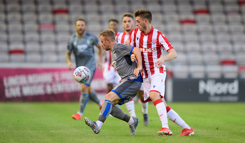 Lincoln City's Joe Morrell shields the ball from Stoke City's Daniel Jarvis<br /> <br /> Photographer Chris Vaughan/CameraSport<br /> <br /> Football Pre-Season Friendly - Lincoln City v Stoke City - Wednesday July 24th 2019 - Sincil Bank - Lincoln<br /> <br /> World Copyright © 2019 CameraSport. All rights reserved. 43 Linden Ave. Countesthorpe. Leicester. England. LE8 5PG - Tel: +44 (0) 116 277 4147 - admin@camerasport.com - www.camerasport.com