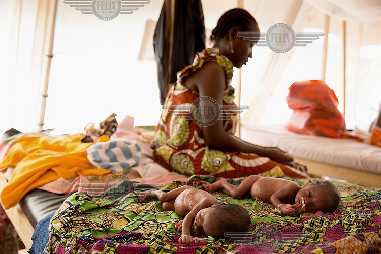 Estella Ngondu (19) sits beside her as yet unnamed twins born prematurely at the Medicins Sans Frontiere (MSF) emergency hospital near the airport in Bangui. Their father was killed by Seleka rebels before their birth.In late 2012 after years of instability and conflict, the Seleka, a predominantly Muslim rebel group, fuelled by grievances against the government, overran the country and, In March 2013, ousted President Francois Bozize, who fled the country. The rebel's leader Michel Djotodia was proclaimed president in August 2013. He disbanded the Seleka in September 2013 but law and order collapsed and ex-Seleka fighters roamed the country committing atrocities against the civilian population. In an attempt to defend their lives and property vigilante groups, calling themselves Anti-Balaka (Anti-Machete), formed to confront the ex-Seleka fighters but soon began to take reprisals against the wider Muslim population and the conflict became increasingly sectarian. By December 2013, with international fears of a genocide being voiced, French led peacekeepers deployed to the country began to act on a UN mandate to disarm the fighters and protect the civilian population. However, they have struggled to contain the situation. Much of the Muslim population, in particular, have been forced into ghettos where they are suffering from food shortages and limited access to healthcare. Often, only a few peacekeepers stand between them and a massacre by vengeful Anti-Balaka militants. UN reports describe 'thousands' killed, while over 600,000 people have been internally displaced and a further 200,000 have fled the county.
