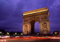 Arc de Triomphe at night with the streaming lights of traffic in motion along the Les Champs Elysees roadway. Paris, France.