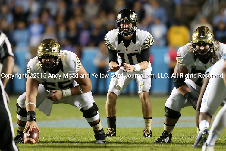 17 October 2015: Wake Forest's John Wolford (10) takes a snap from Josh Harris (65). The University of North Carolina Tar Heels hosted the Wake Foresst University Demon Deacons at Kenan Memorial Stadium in Chapel Hill, North Carolina in a 2015 NCAA Division I College Football game. UNC won the game 50-14.