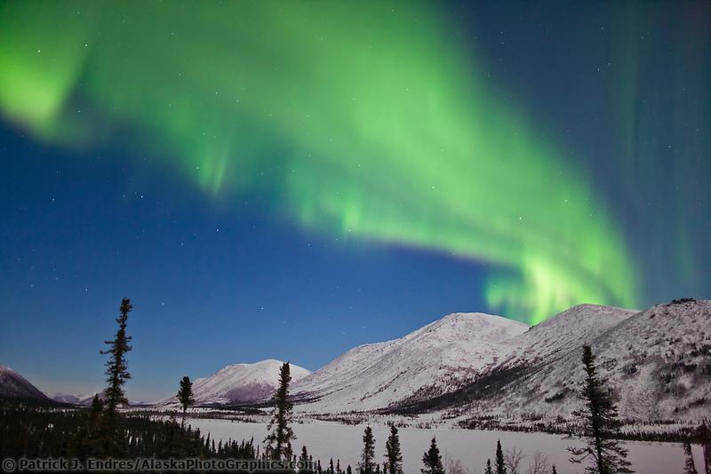 Aurora borealis arcs across the sky over the Brooks mountains at Grayling Lake, Arctic, Alaska