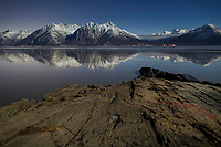 winter landscape of moonlight on shoreline of Turnagain Arm with Chugach Mountains