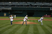OAKLAND, CA - AUGUST 14:  Oakland Athletics team photographer Michael Zagaris, photographer Ron Riesterer, and photographer Doug McWilliams throw out the ceremonial first pitches before the game between the Kansas City Royals and Oakland Athletics at the Oakland Coliseum on Monday, August 14, 2017 in Oakland, California. (Photo by Brad Mangin)