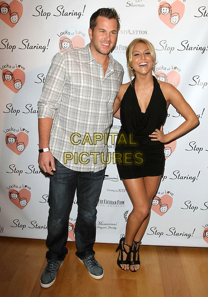 DOUG REINHARDT & CASSIE SCERBO.Charitable event to benefit ìLocks of Loveî held at Sky Bar at The Mondrian, West Hollywood, CA, USA.  .October 6th, 2010.full length jeans denim grey gray check shirt white black halterneck dress hand on hip smiling laughing .CAP/ADM/KB.©Kevan Brooks/AdMedia/Capital Pictures.