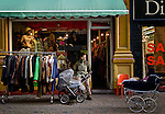 BRUSSELS - BELGIUM - 07 JANUARY 2012 -- Marolles the bohemian city part of Brussels. -- Second hand cloths shop on Rue Blaes with waiting young father and baby carriage. -- PHOTO: Juha ROININEN /  EUP-IMAGES