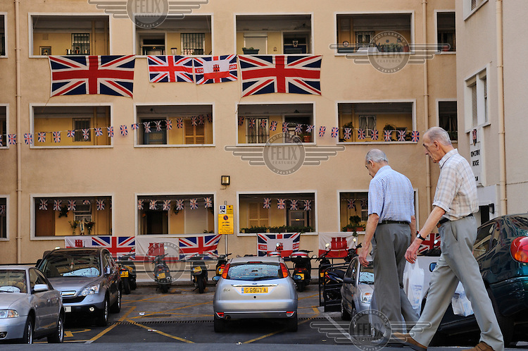 Residents going home to their apartment building, decorated with British and Gibraltan flags in preparation for Gibraltar National Day celebrations.