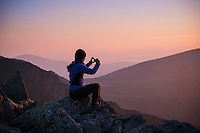 Female hiker takes photo of sunset from summit of Glyder Fach, Snowdonia national park, Wales
