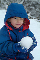 Three year old girl making a snowball, Selonnet, French Alps, France.