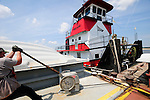 {8/24/12} {10pmCST} -JOB # 42286- Greenville , MS, U.S.A. --Workers for Wepfer Marine of Greenville MS. tie barges together and then tether tehm to shore, in a big holding pattern alomg the bansk of the Mississsippi RIver beacuse the water level is causing a back up of barge traffic.  Historically low river levels on the Mississippi River are causing havoc on river traffic: grounding barges loaded with grain and fertilizer, traffic jams several miles long and forcing the Coast Guard to close down chunks of the river due to groundings. The area around Greenville, Miss., has closed three times the past week due to groundings. Last year, there were five total groundings the entire low-water season. Locals who fought historic high-water floods last year are this year engaged in a different fight: keeping barges afloat on a vanishing Mississippi.  -- Photo by Suzi Altman, Freelance.