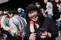 A Japanese woman sucks on a penis shaped candy during the Kanamara matsuri or festival of the iron phallus in Kawasaki Daishi near Tokyo, Japan. Sunday April 1st 2012