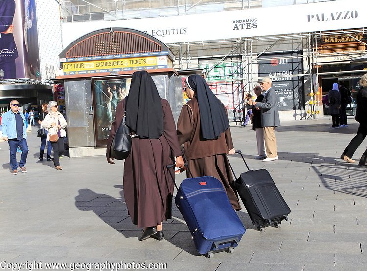 Two nuns wearing brown habits each pulling a suitcase in Madrid city centre, Spain