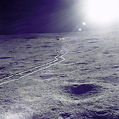 """The Apollo 14 Lunar Module (LM) """"Antares"""" is photographed against a brilliant sun glare during the first Apollo 14 extravehicular activity (EVA-1) on February 5, 1971. A bright trail left in the lunar soil by the two-wheeled Modularized Equipment Transporter (MET) leads from the LM.<br /> Credit: NASA via CNP"""