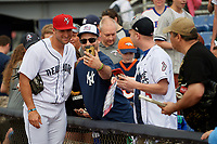 Binghamton Rumble Ponies left fielder Tim Tebow (15) takes a picture with a fan prior to a game against the Erie SeaWolves on May 14, 2018 at NYSEG Stadium in Binghamton, New York.  Binghamton defeated Erie 6-5.  (Mike Janes/Four Seam Images)