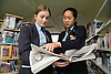 Secondary school students looking at a newspaper in the school library,