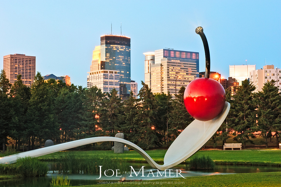 Spoonbridge and Cherry sculpture in front of Minneapolis skyline at sunset.  Designed by Claes Oldenburg and his wife, Coosje van Bruggen.  The complex fabrication of the 5,800 pound spoon and 1,200 pound cherry was carried out at two shipbuilding yards in New England. The sculpture has become a beloved icon in the Garden, whether glazed with snow in the Minnesota winters or gleaming in the warmer months, with water flowing over the surface of the cherry and a fine mist rising from its stem.