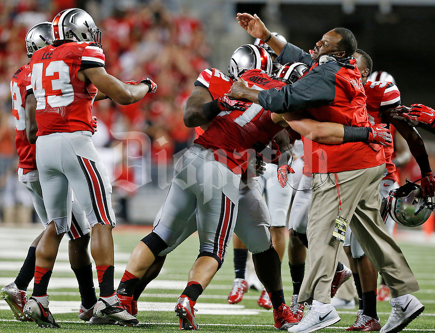 Ohio State Buckeyes defensive lineman Joey Bosa (97) celebrates on the sidelines after tackling Virginia Tech Hokies quarterback Michael Brewer (12) and causing a fumble recovered by the Buckeyes during Saturday's NCAA Division I football game at Ohio Stadium in Columbus on September 6, 2014. Virginia Tech won the game 35-21. (Dispatch Photo by Barbara J. Perenic)