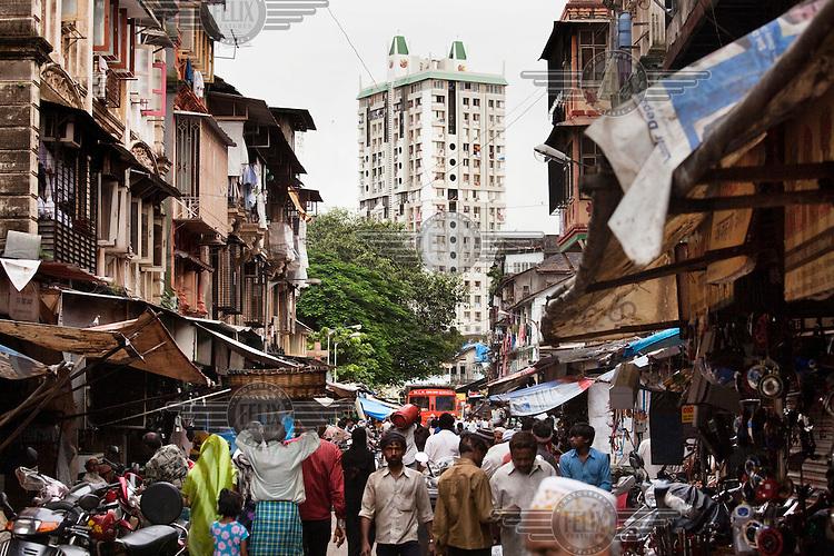 A modern apartment block is seen from a street market..